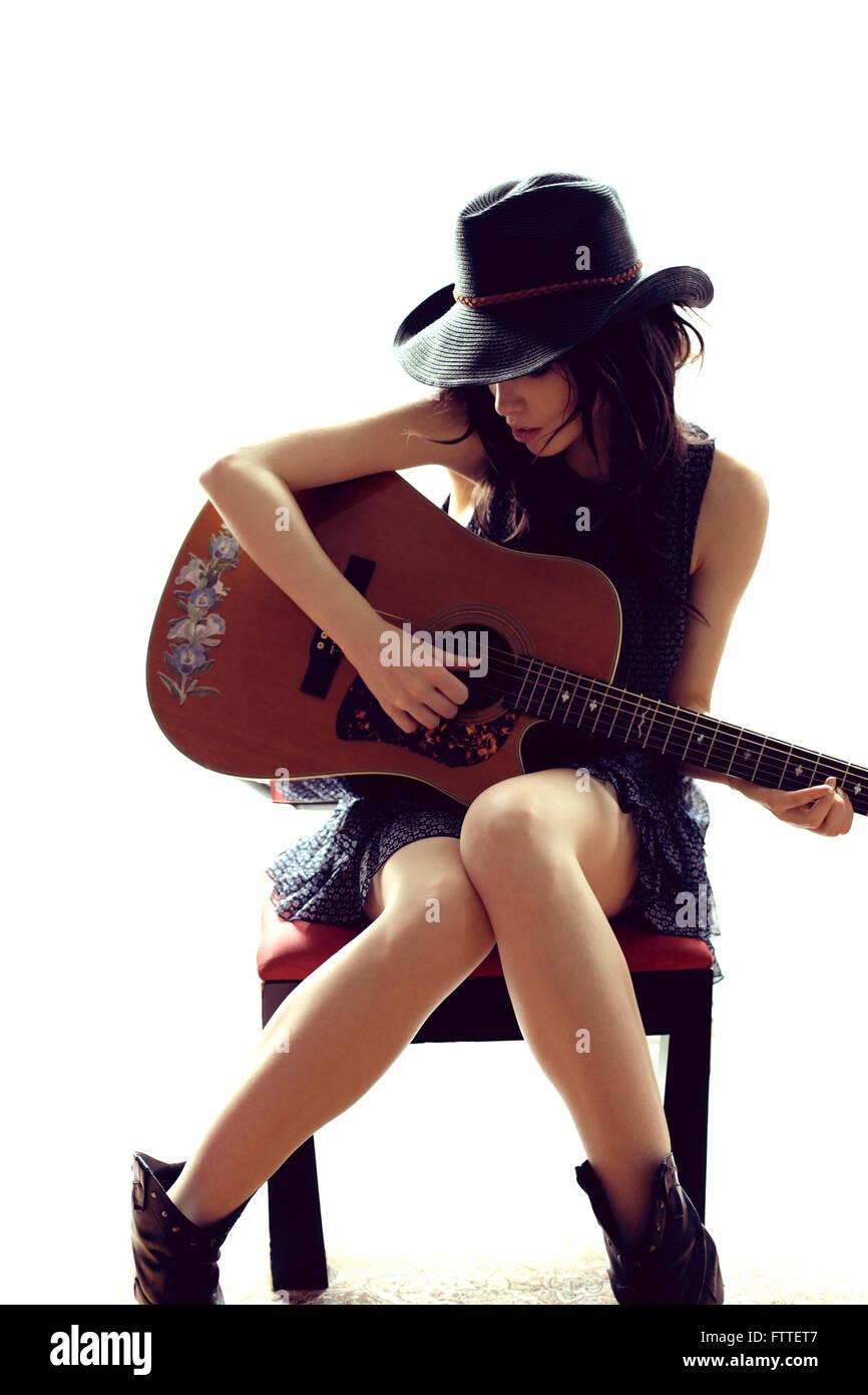 Brünette Frau sitzen, Gitarre spielen Stockbild