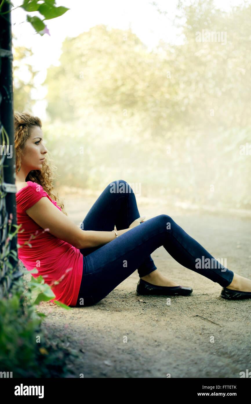 Lässige junge Frau sitzt im park Stockbild