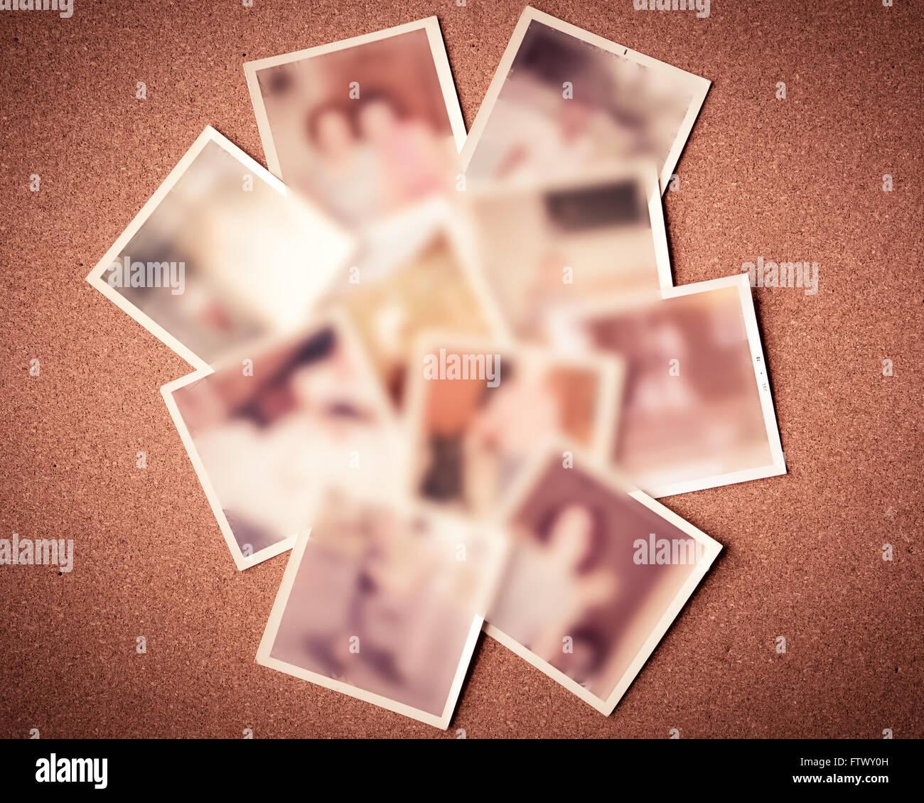 Defokussierten Unschärfe der verstreuten alten Familienfotos gegen Pinnwand Stockbild