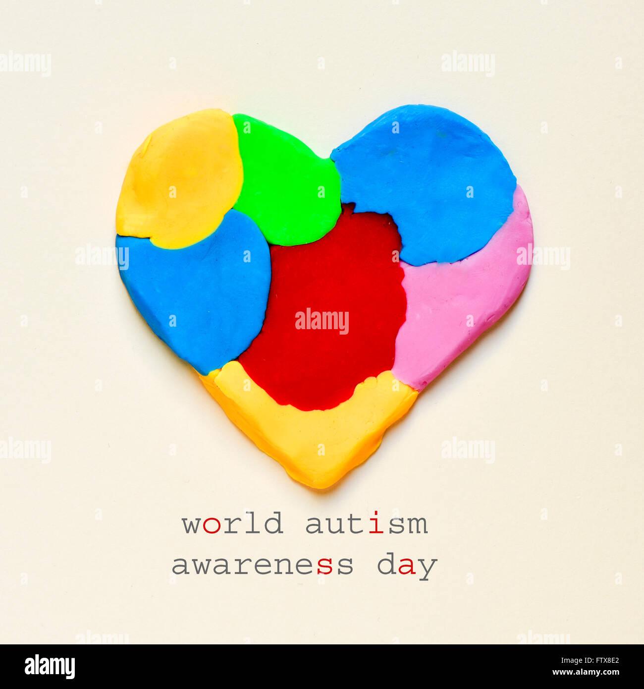 der Text Autismus Welttag der Aufklärung und ein Herz aus Knetmasse in verschiedenen Farben auf eine wollweiße Stockbild