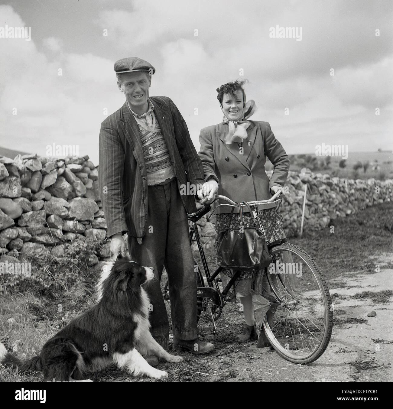 1950er Jahre historische, beenden Sie westlich von Irland, irische Bauern mit Schäferhund und Frau mit dem Stockbild