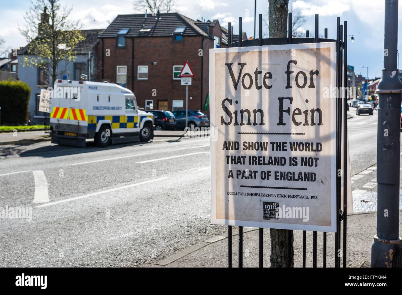 Stimmen Sie für Sinn Féin Wahlplakat auf Belfast Falls Road mit PSNI Land Rover im Hintergrund geparkt. Stockbild