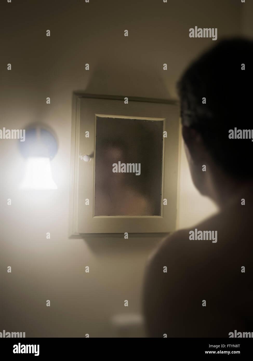 Man stellt seine düsteren Bild im Spiegel. Stockbild