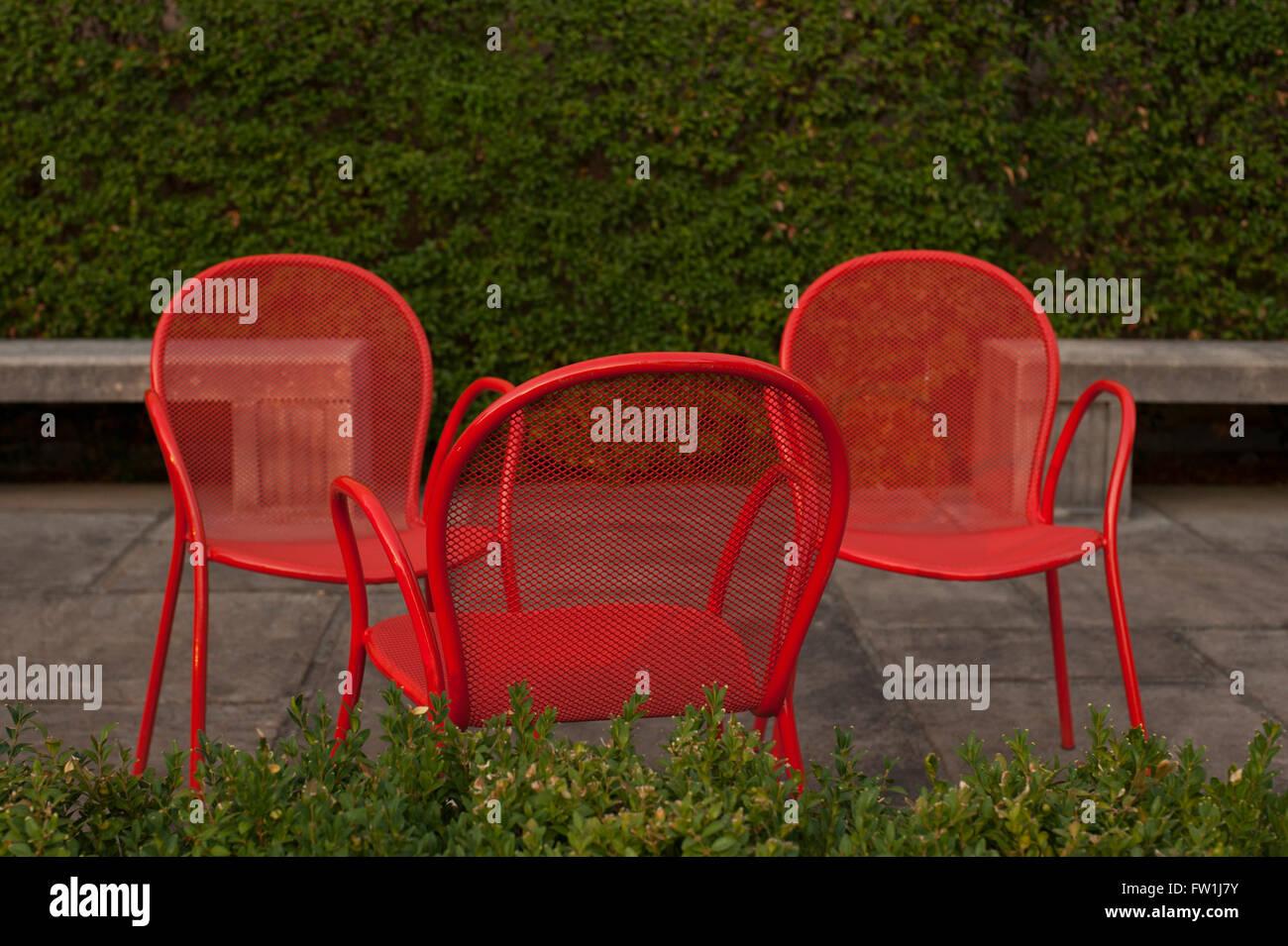 Rote Stühle auf der Terrasse mit Hecke Stockbild