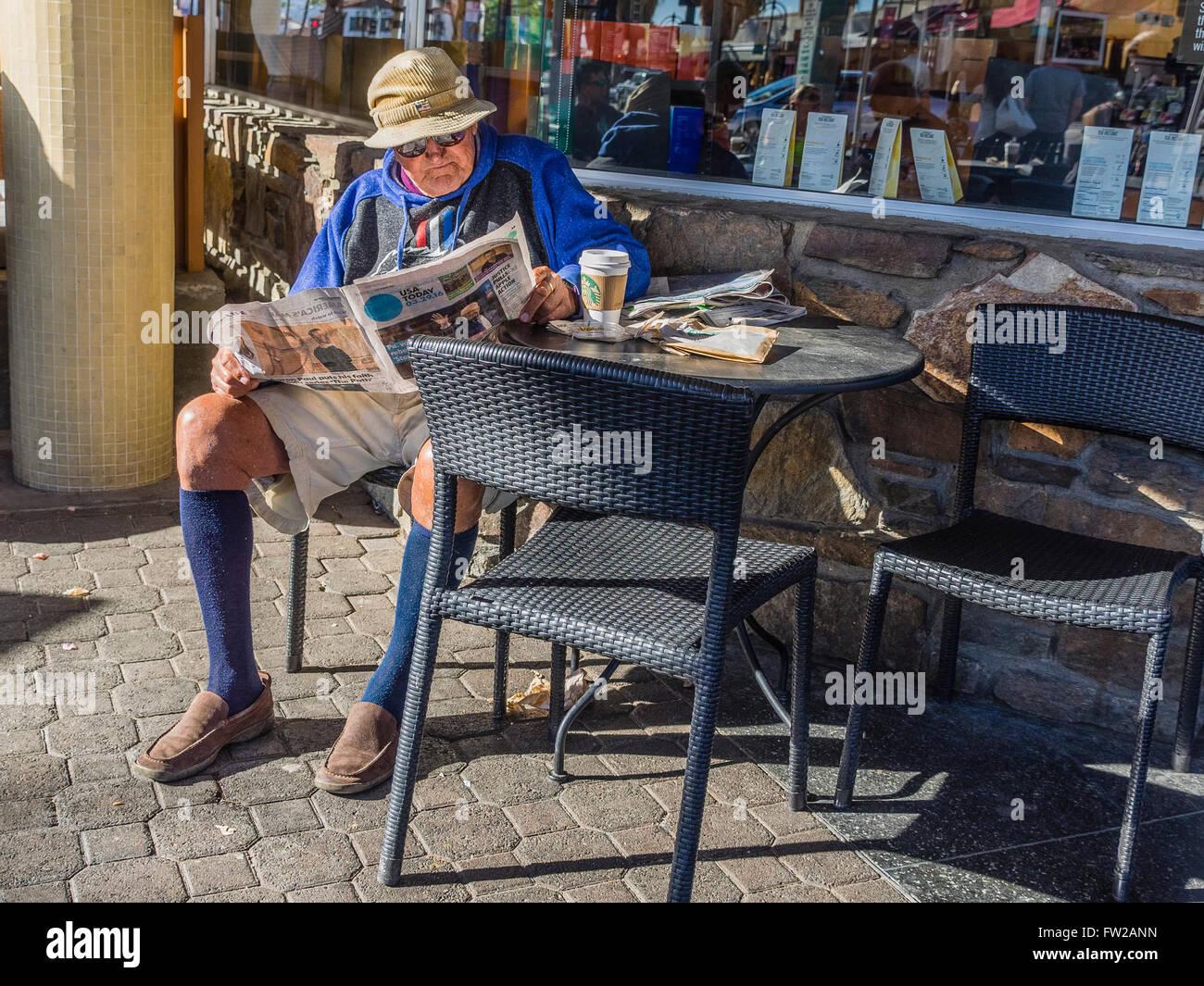 Männliche Senioren Lesen einer Zeitung in einem Café im frühen Morgenlicht. Stockbild