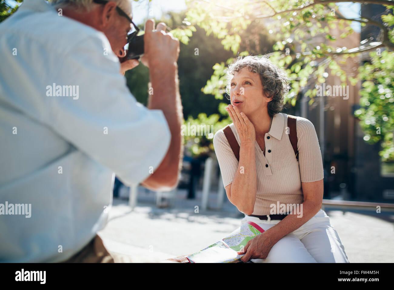 Schöne ältere Frau bläst einen Kuss und Kamera im freien sitzend auf einer Bank in der Stadt. Frau Stockbild