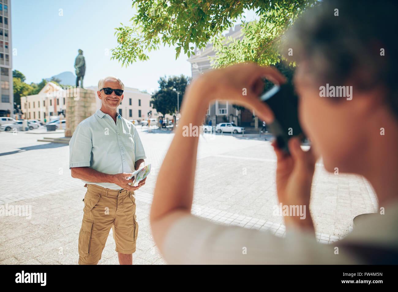 Senior woman für Fotos zu posieren. Mann von seiner Frau im Urlaub fotografiert. Stockbild