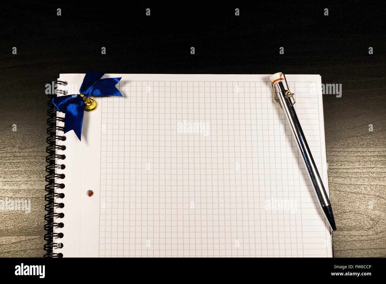 Notebook mit leeren Seiten öffnen und Bleistift auf schwarzem Hintergrund aus Holz Stockfoto