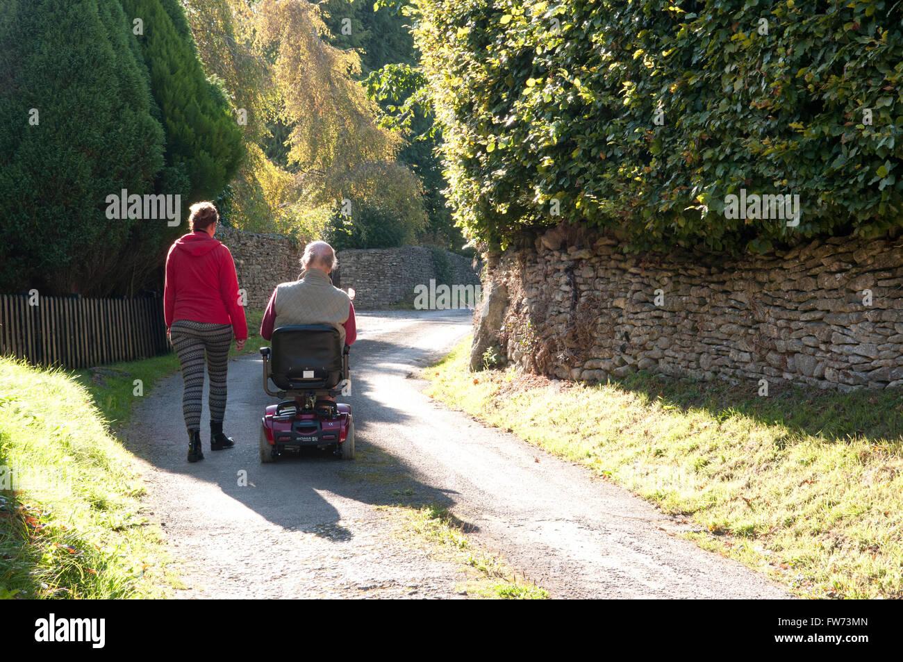 Rückansicht eines älteren Mannes mit seinem Betreuer zu Fuß neben ihm ein Elektromobil Stockbild