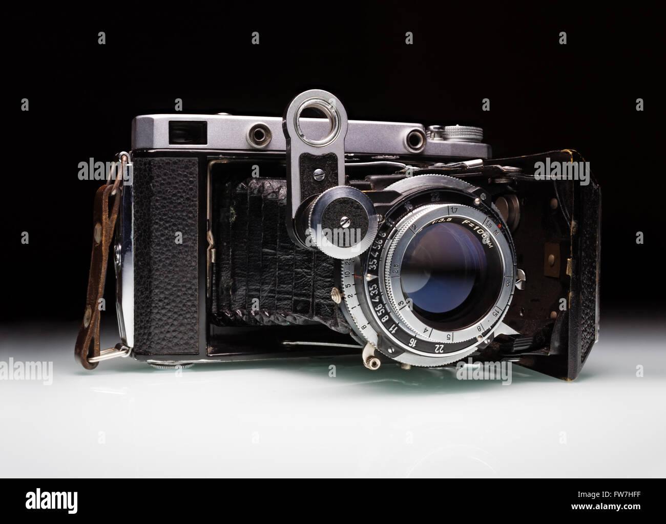 Eine sehr alte Falten Bälge Kamera vor einem schwarzen Hintergrund, Studio gedreht Stockbild