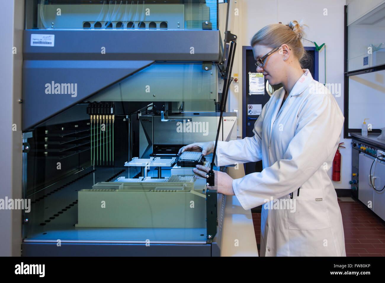 Wissenschaftler an einem Pipettierroboter Stockbild