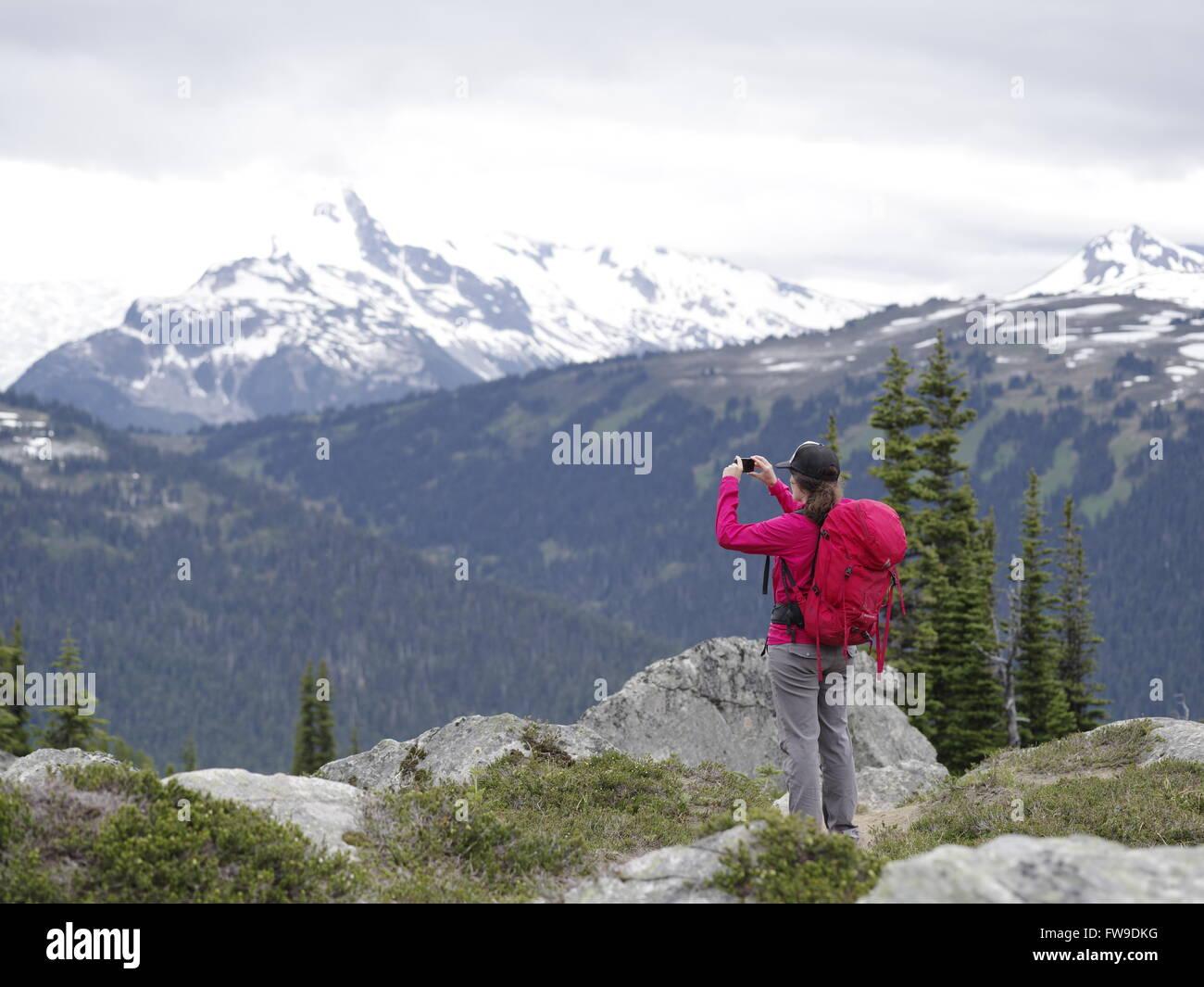 Eine junge weibliche Wanderer auf Berggipfel und hält ein smart Phone in Whistler Blackcomb Höhenwanderung, Stockbild