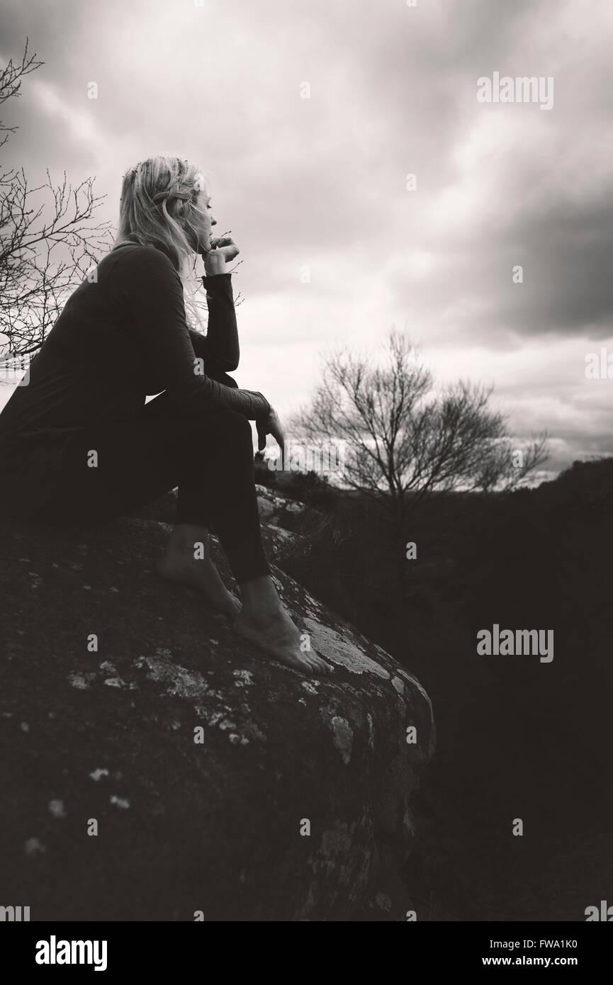 Profil der jungen Frau auf den Felsen sitzen und denken Stockbild