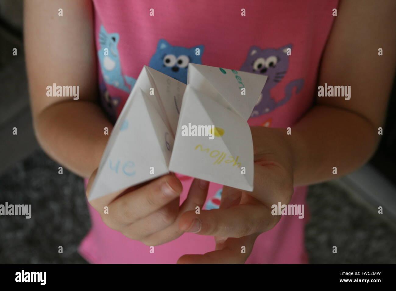 Kind hält Origami Wahrsagerin Stockbild
