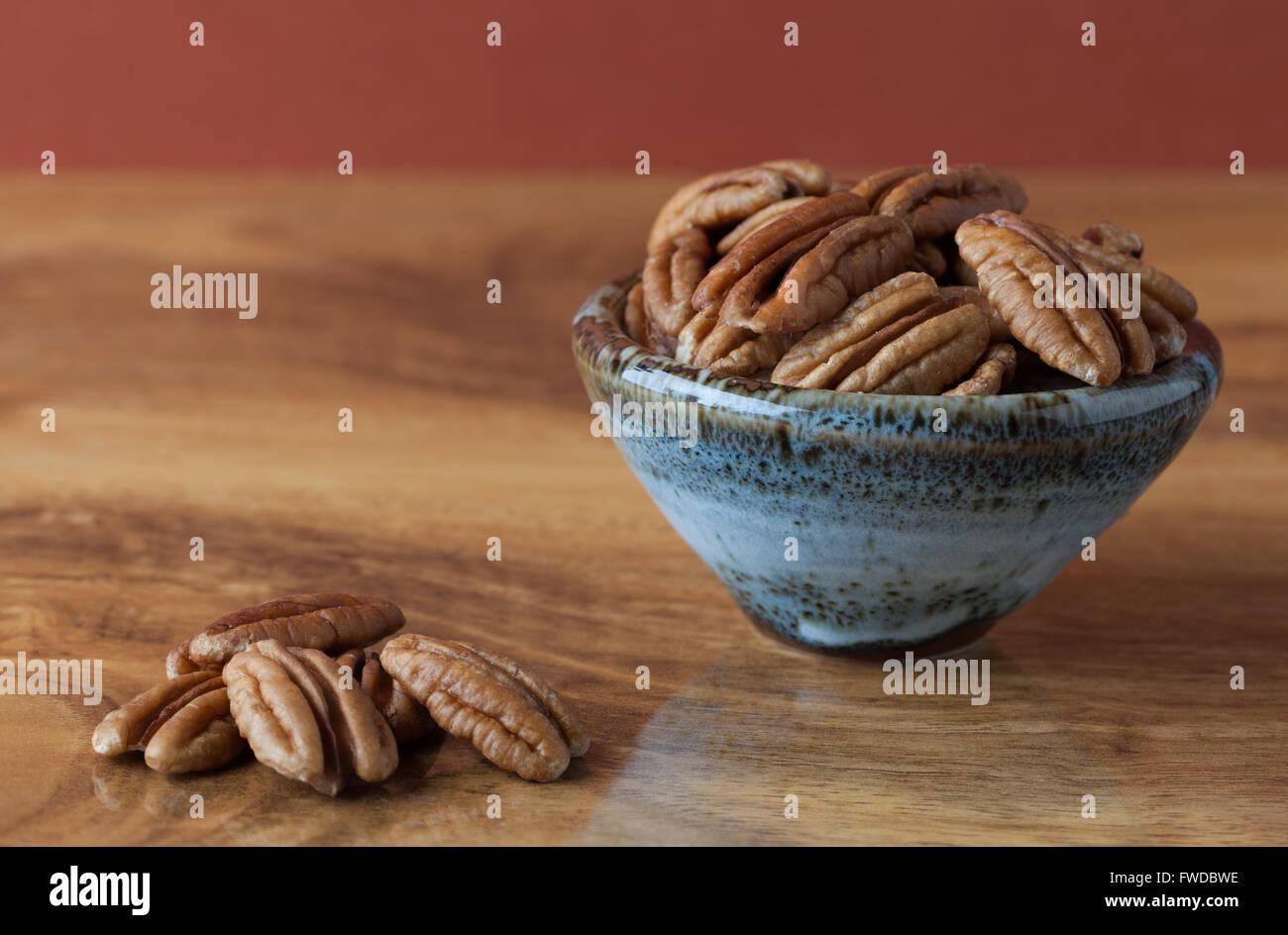 Pekannüsse auf Holztisch und in Keramikschale mit braunem Hintergrund. Textfreiraum, geringe Schärfentiefe Stockbild