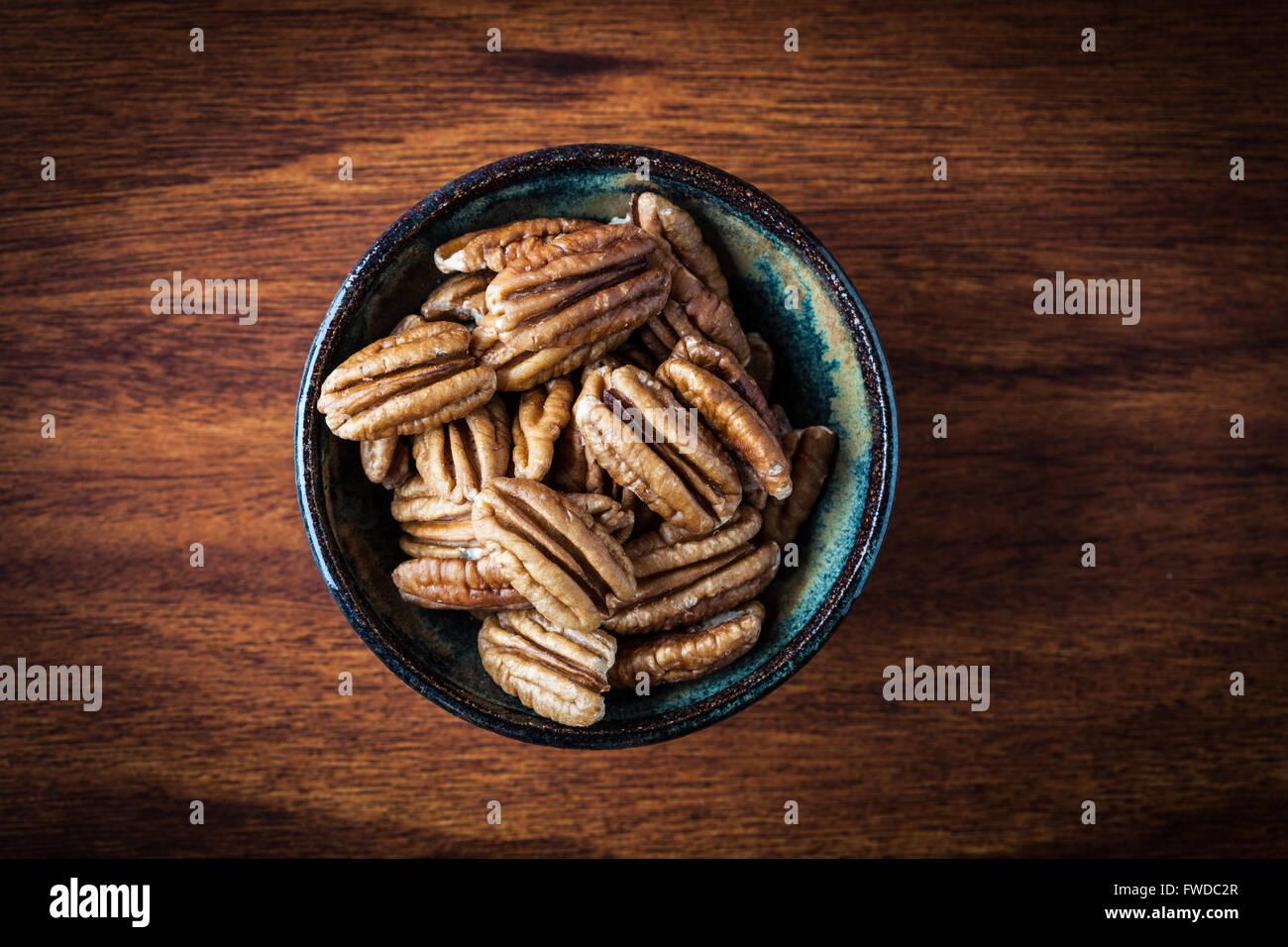 Pekannüsse in Keramikschale auf Holztisch. Geringe Schärfentiefe. Ansicht von oben. Stockbild