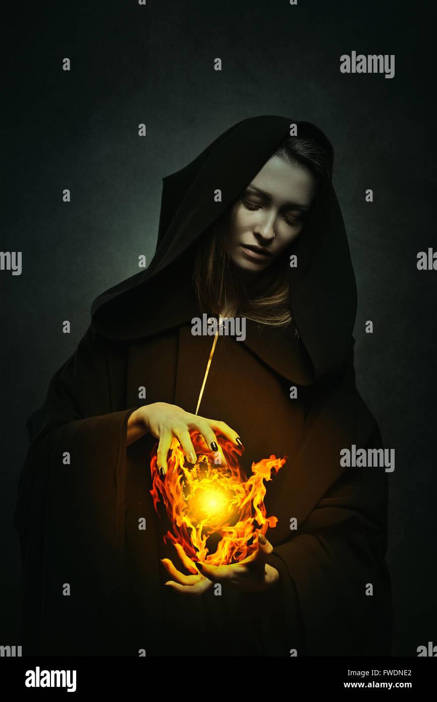 Dunkle Zauberin Casting magischen Flammen. Fantasie-Porträt Stockfoto