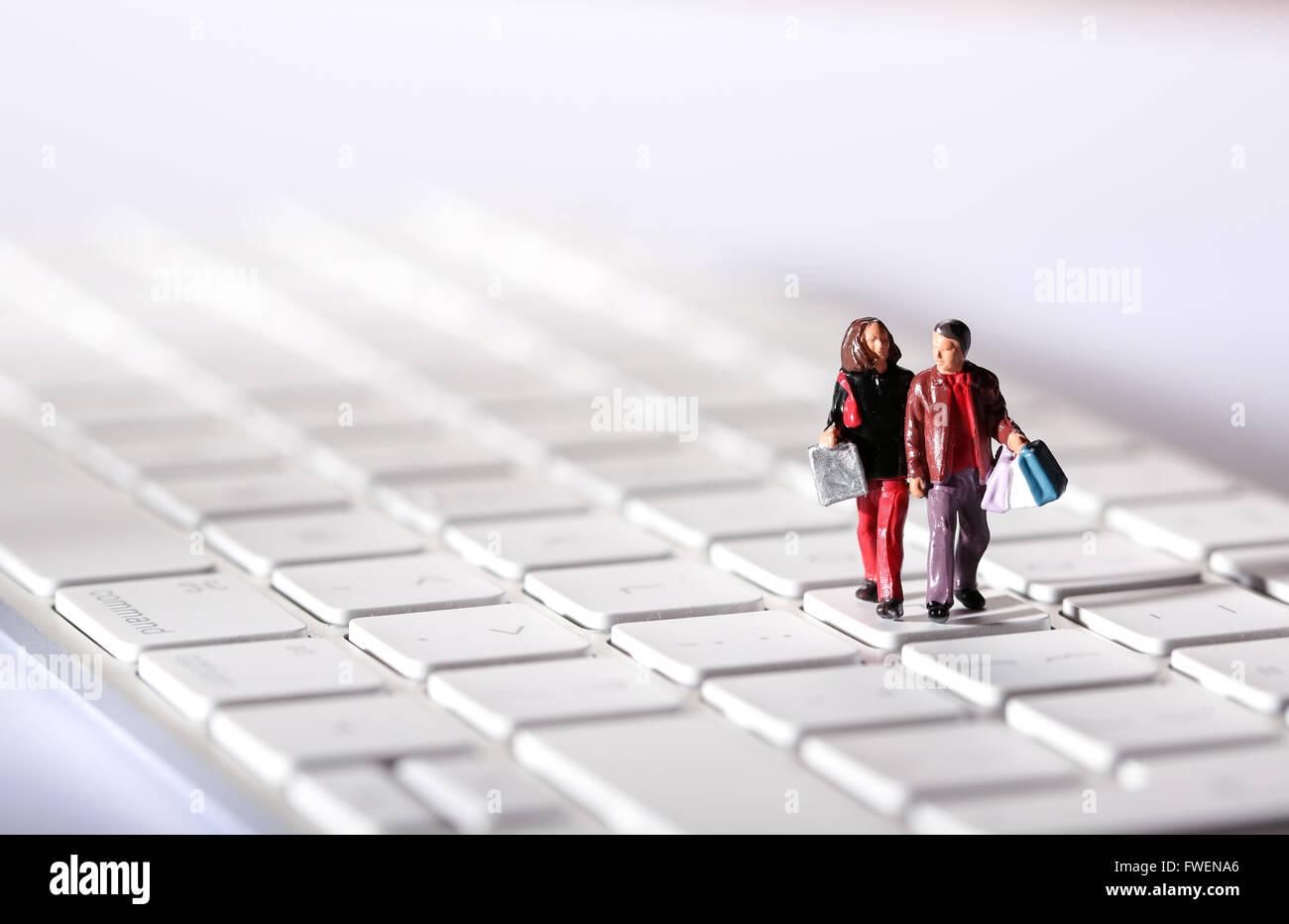 Online-Shopping-Konzept-Bild eines Paares auf einer Computertastatur Einkaufstaschen tragen Stockbild