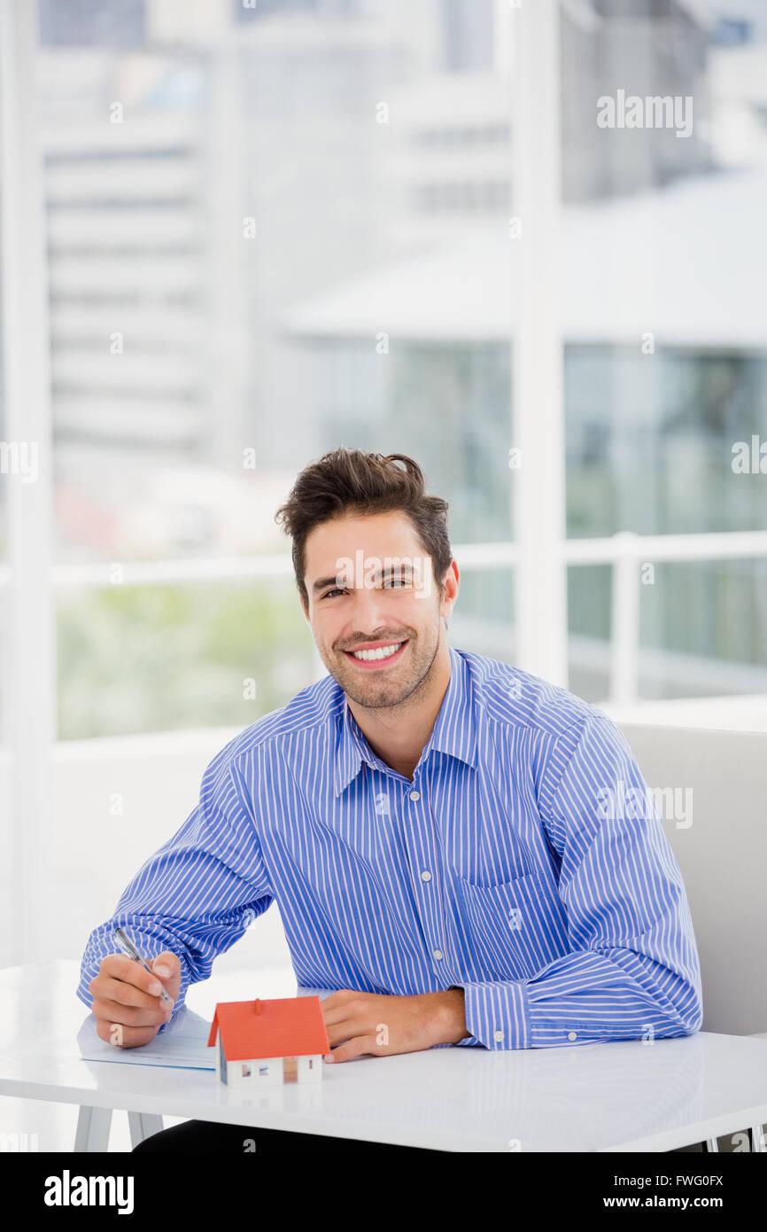 Geschäftsmann mit einem Musterhaus schreiben auf Papier Stockbild