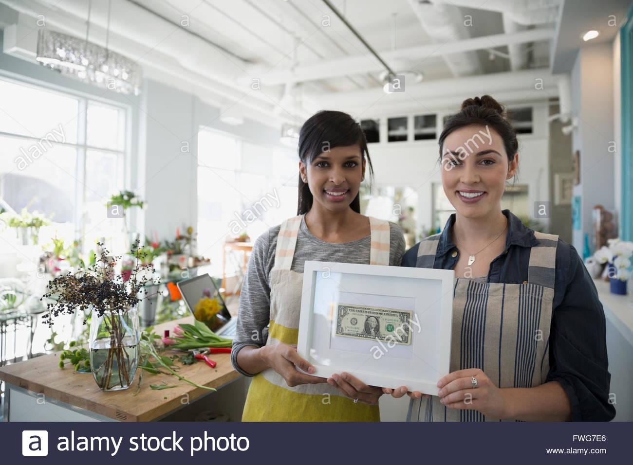 Porträt zuversichtlich Floristen halten gerahmte ersten verdienten dollar Stockbild