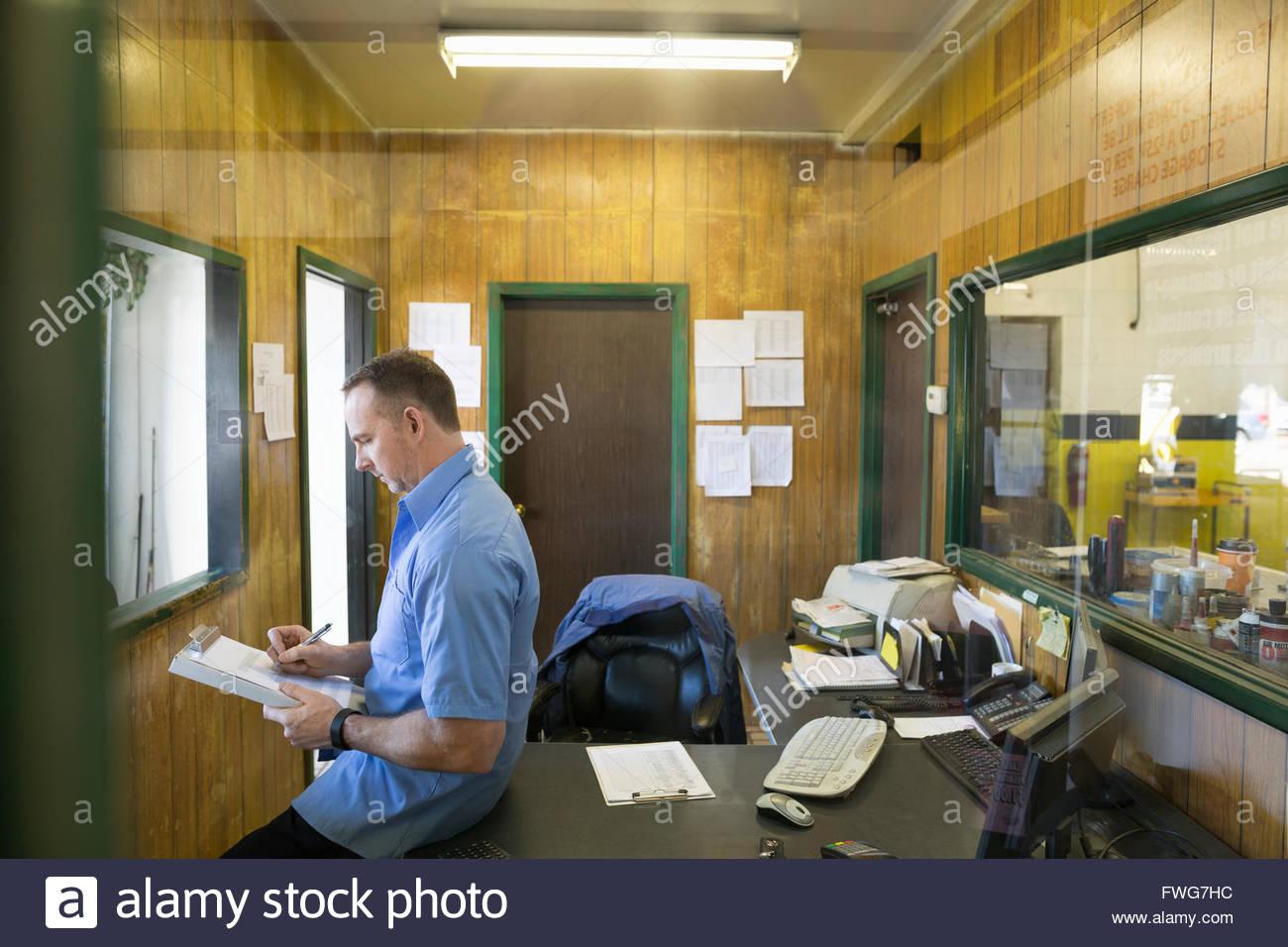 Mechaniker in Zwischenablage im Auto-laden-Büro schreiben Stockbild