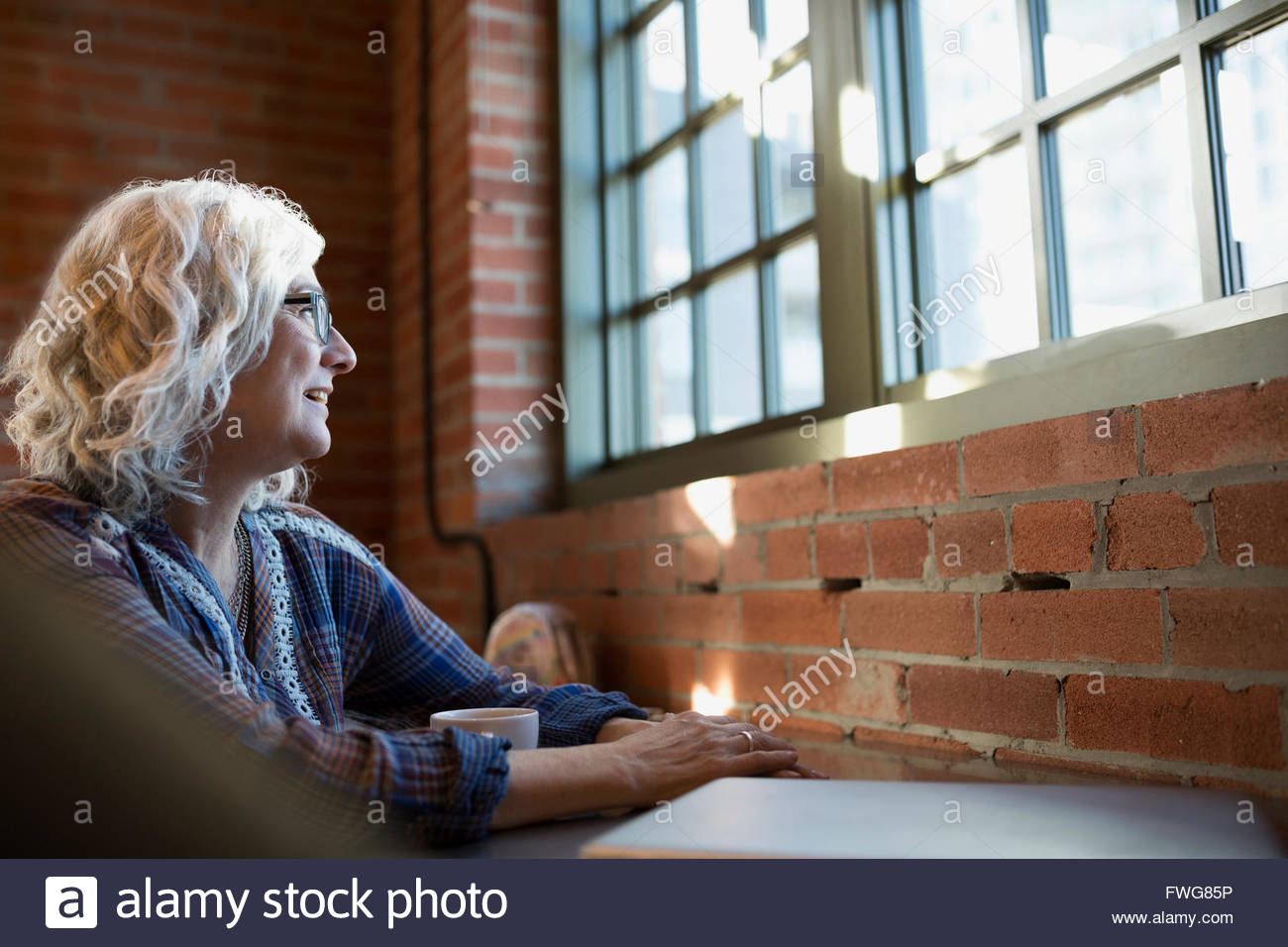 Nachdenkliche Frau trinkt Kaffee in Coffee-shop Stockbild