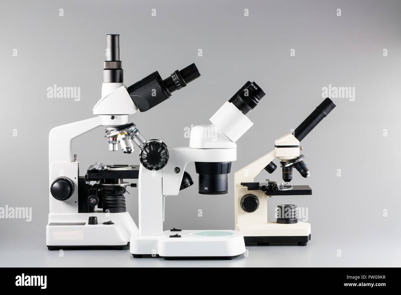 Monokular fernglas und trinocular mikroskope vor einem grauen