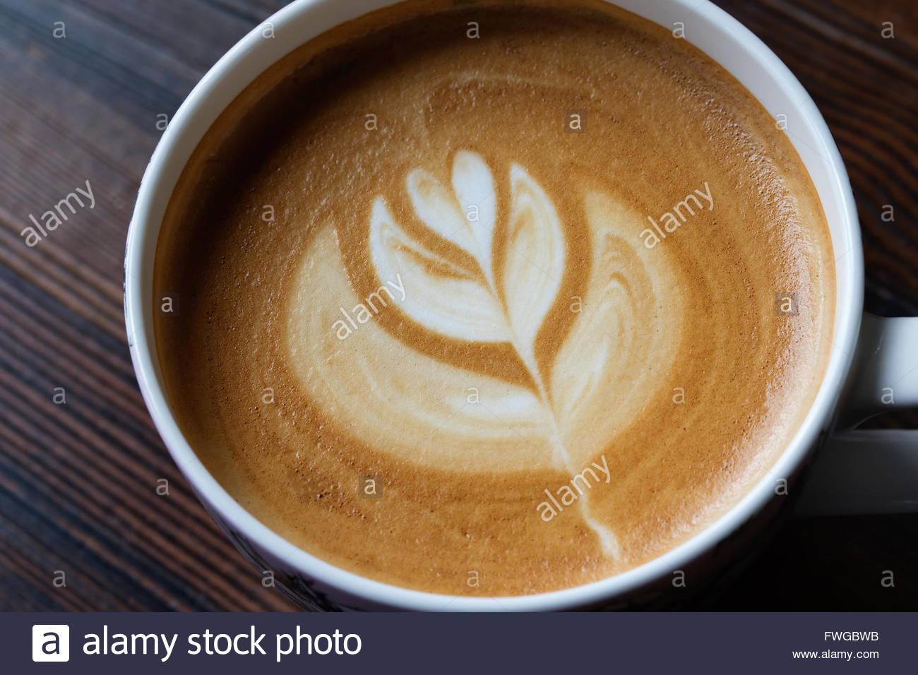 Tasse Latte Art Kaffee auf Holztisch Stockbild