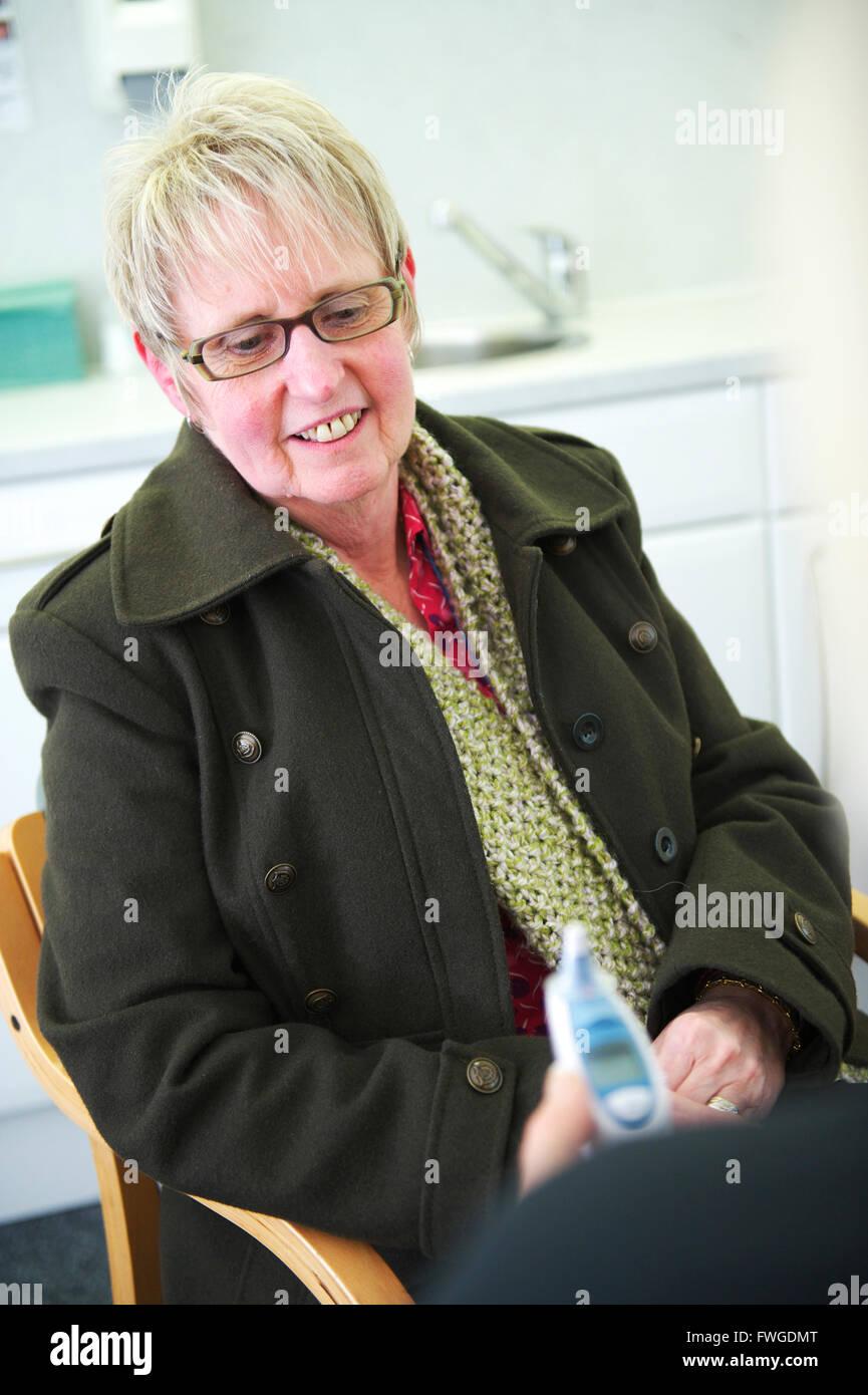 Applying britische Frau, die glücklich diskutieren Ergebnisse mit General Practitioner (GP) in der NHS-Chirurgie Stockbild