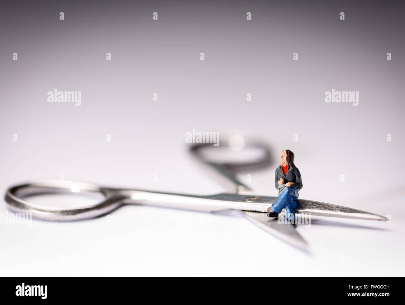 Vasektomie-Konzept-Bild einer Miniatur Figur Schneidersitz saß auf der Schere Stockbild