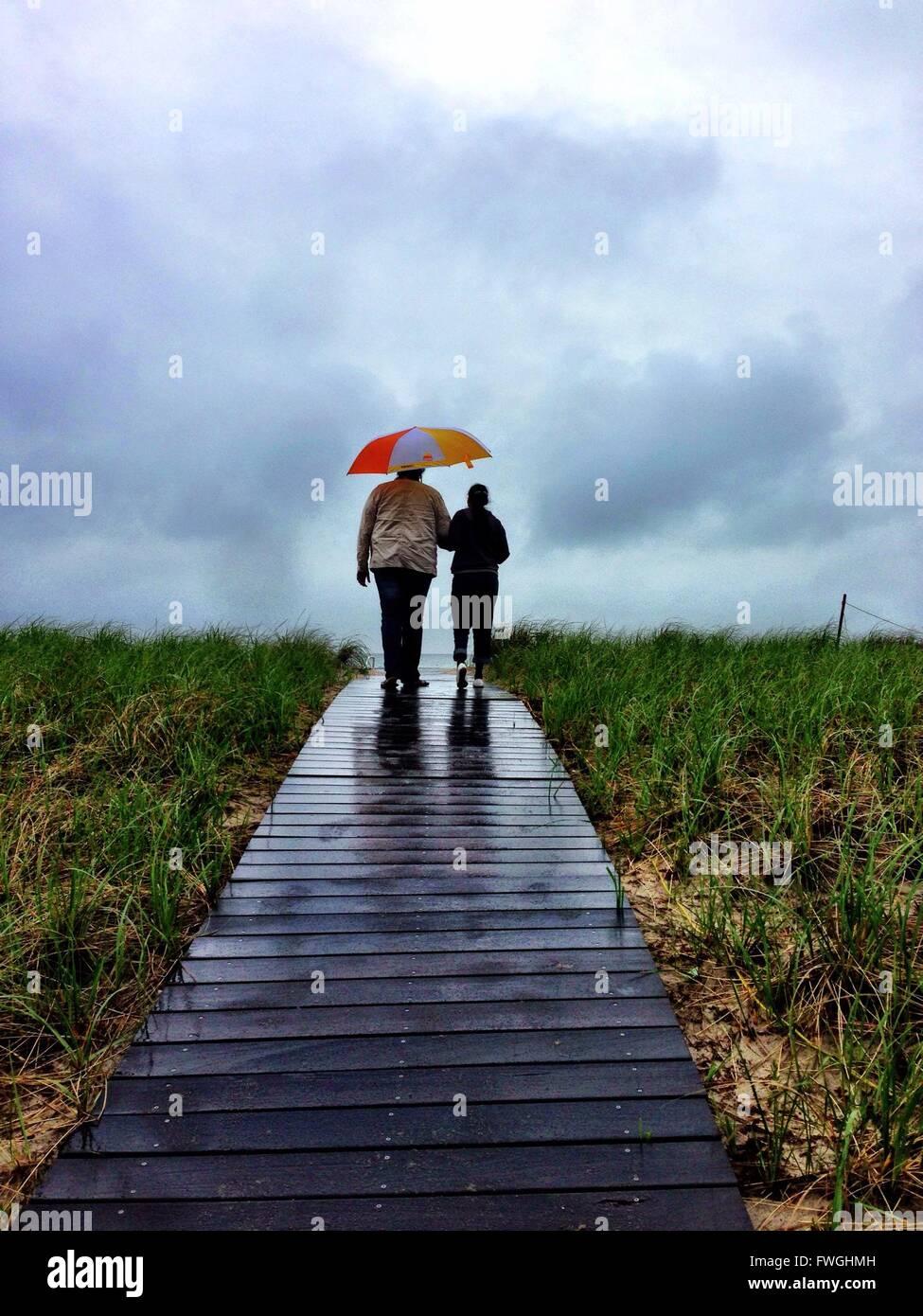 Rückansicht des Paares zu Fuß auf der Promenade Stockbild