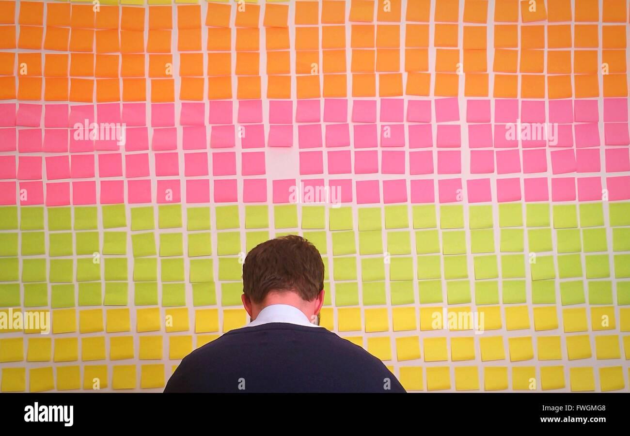 Rückansicht des Kaufmanns gegen bunte selbstklebende Notizen an Wand im Büro Stockbild