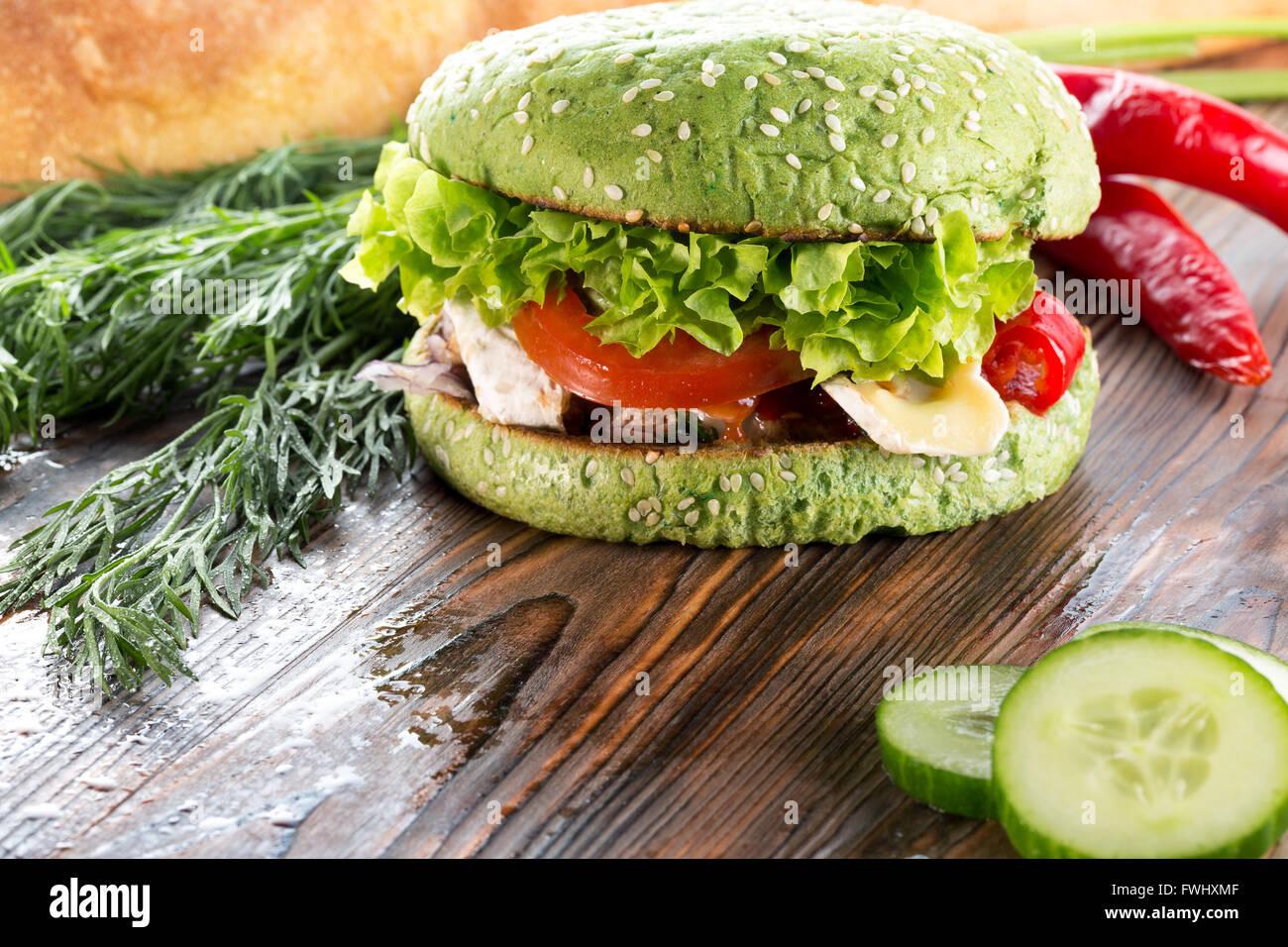 Burger mit grünen Brötchen auf hölzernen Hintergrund. Stockbild