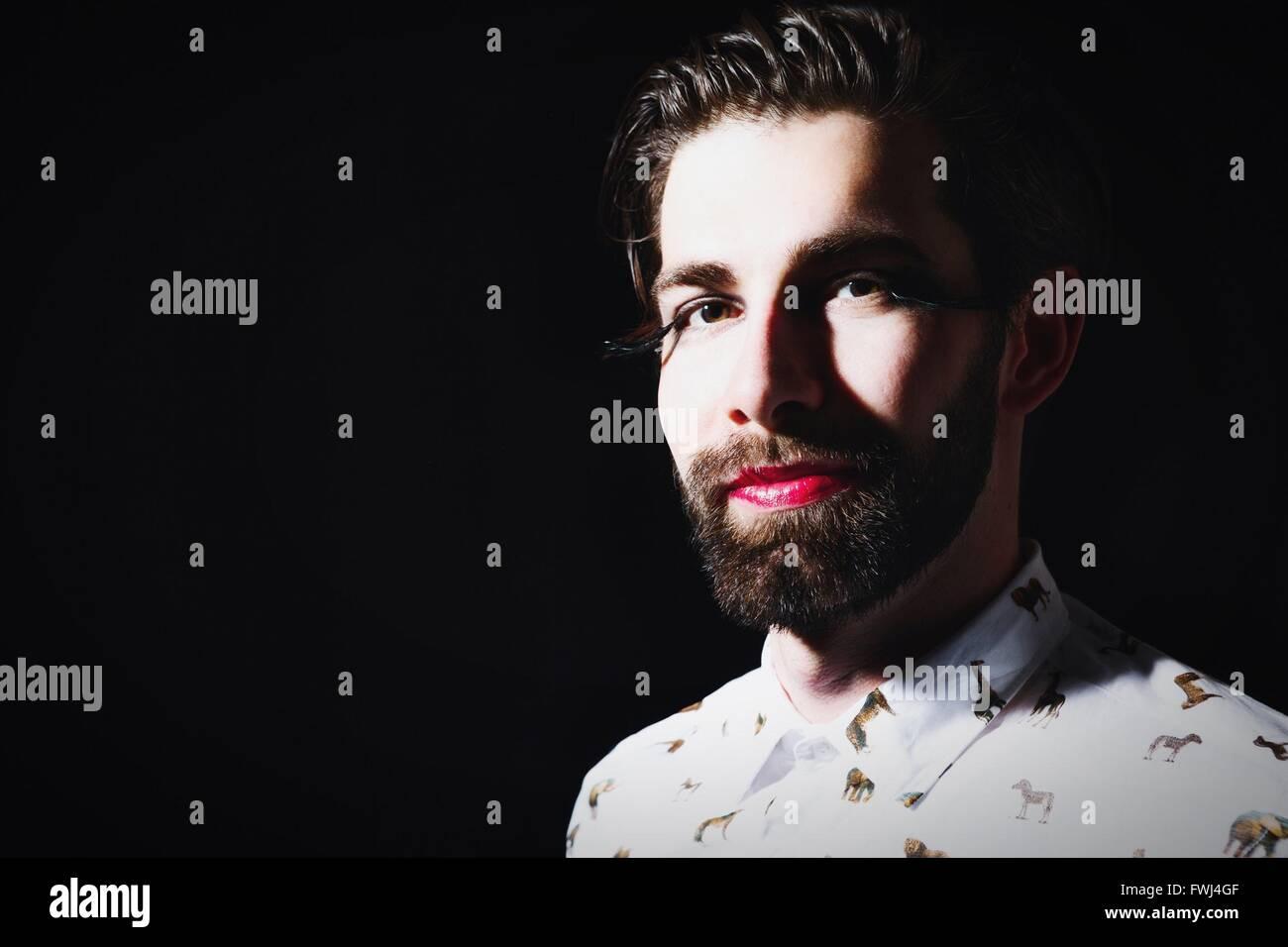 Porträt des Mannes mit rotem Lippenstift In künstliche Wimpern auf schwarzem Hintergrund Stockbild