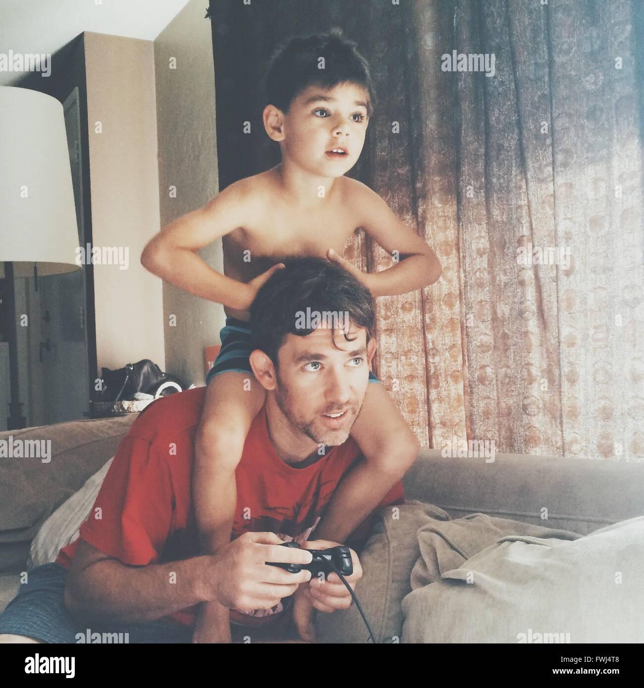 Vater und Sohn spielen Videospiel zu Hause Stockbild