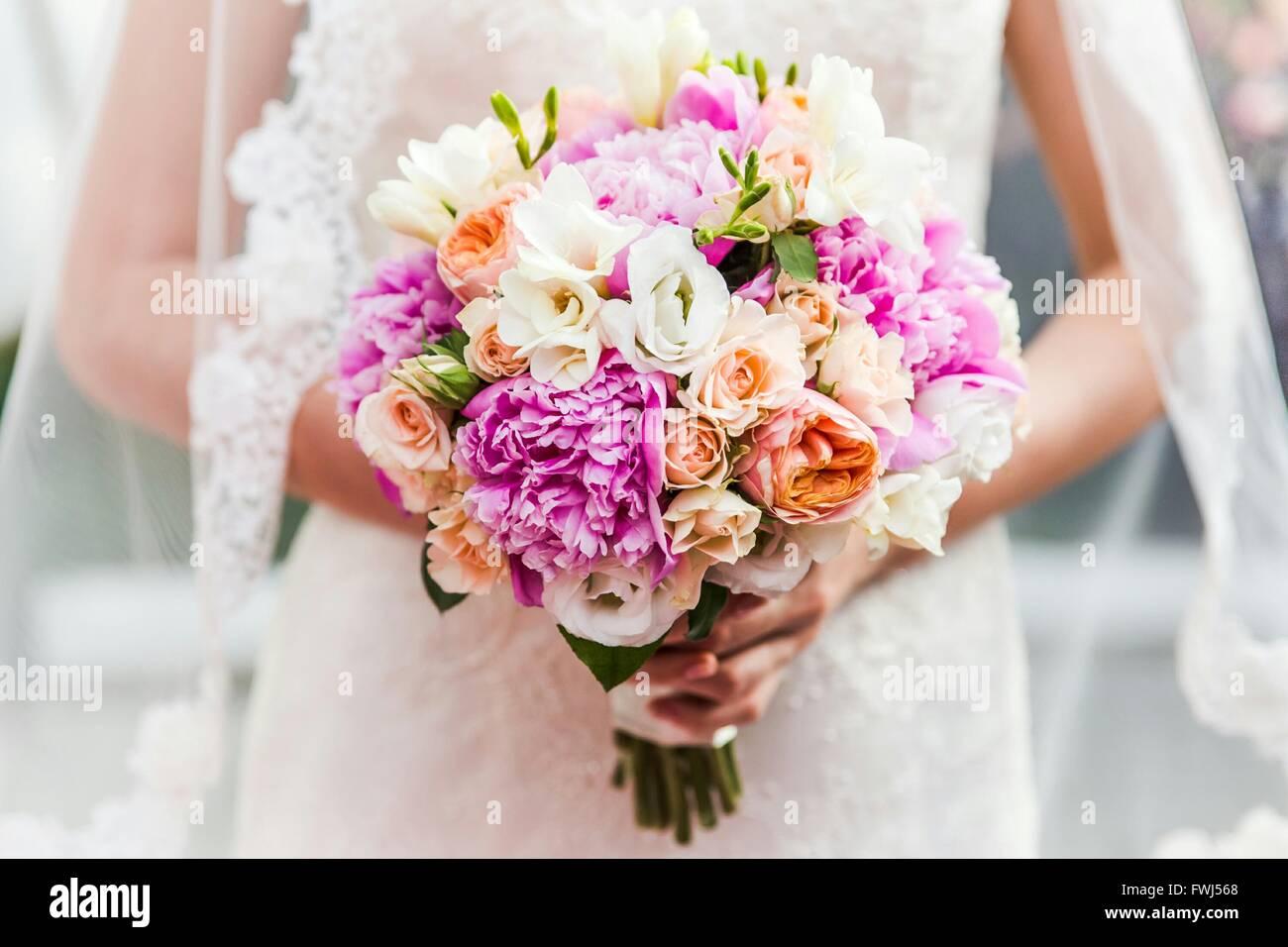 Mittelteil der Braut hält Blumenstrauss Stockbild