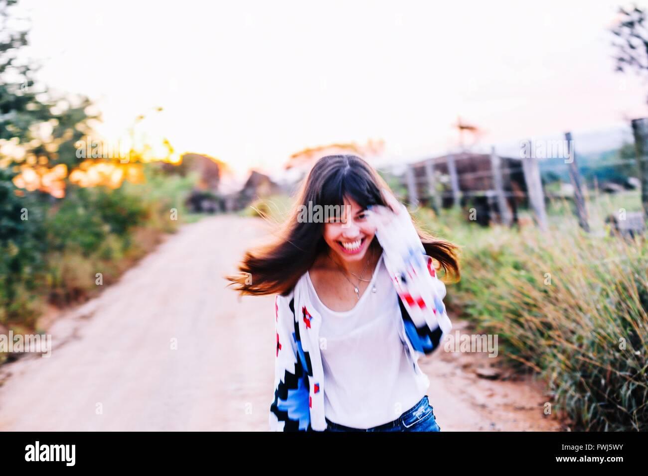 Porträt der glückliche junge Frau läuft auf der Straße inmitten von Pflanzen gegen klaren Himmel Stockbild