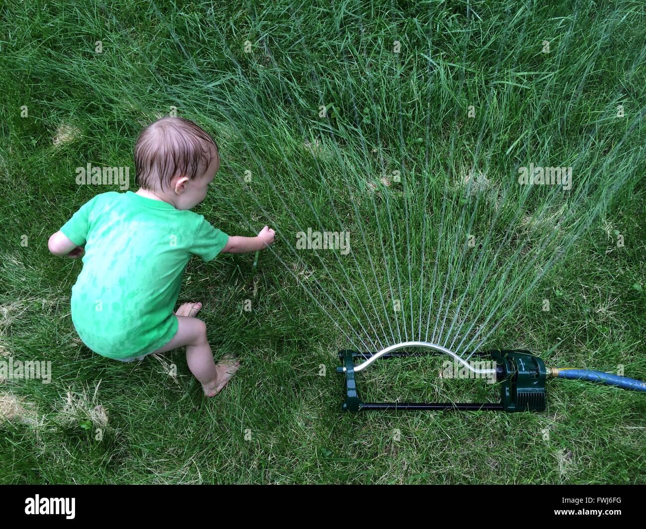 High Angle View Of Kind spielt durch Sprinkler auf Wiese Stockbild
