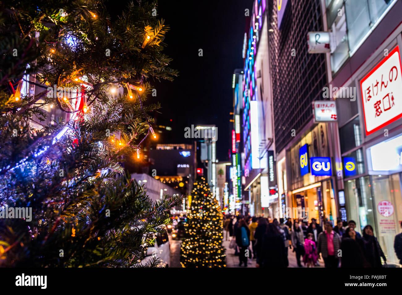 Menschen auf der Straße entlang gebaut Strukturen und beleuchtete Bäume Stockbild