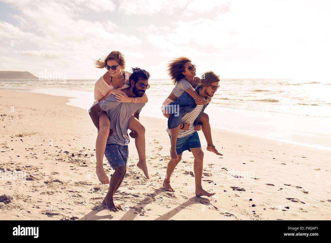 Zwei schöne junge Paare zu Fuß am Strand entlang, mit Männern geben Huckepack Fahrt für Frauen. Stockbild