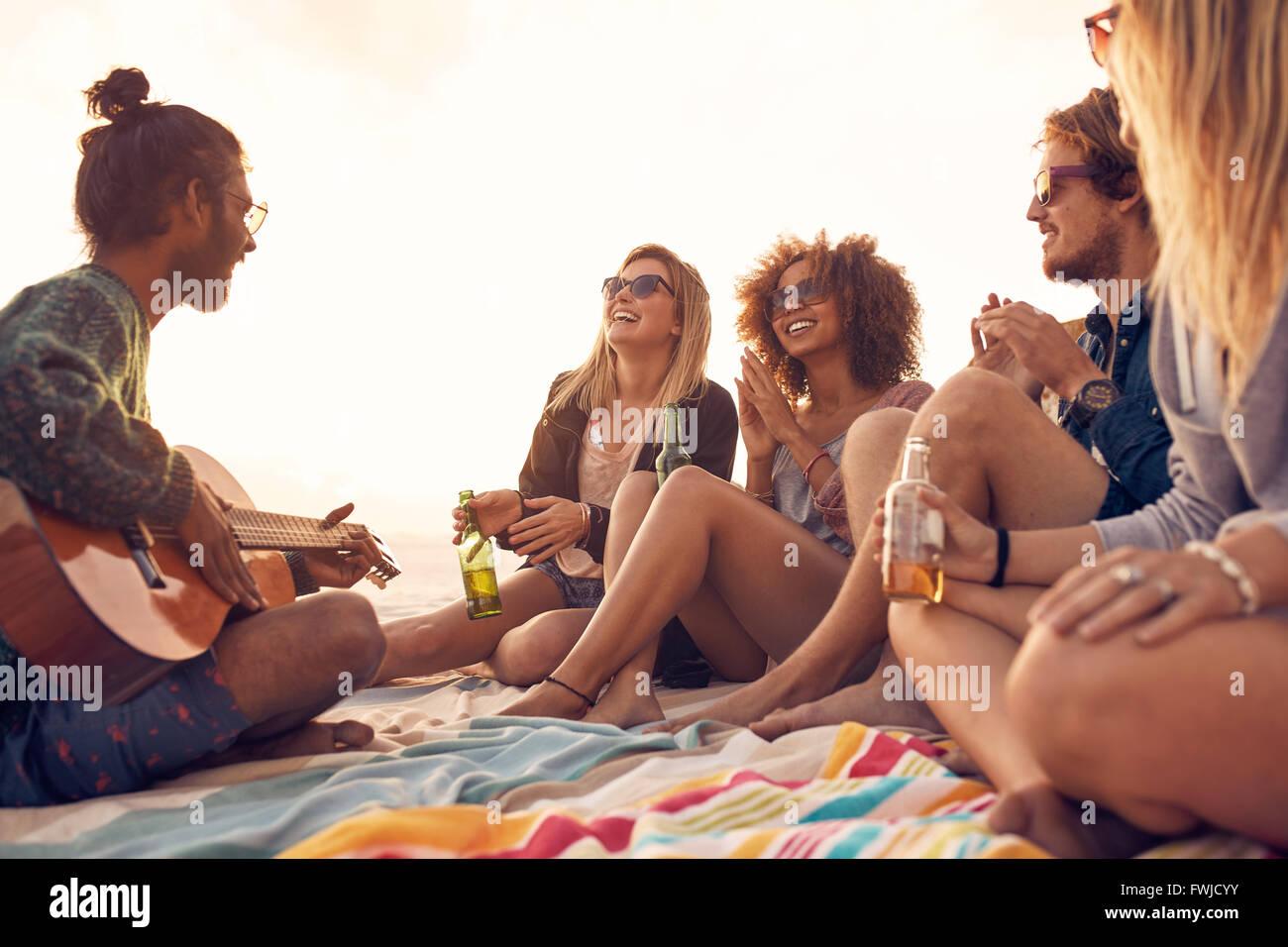 Glücklich Hipster, entspannen und spielen Gitarre am Strand. Freunde, trinken Bier und Musik hören. Spaß Stockbild