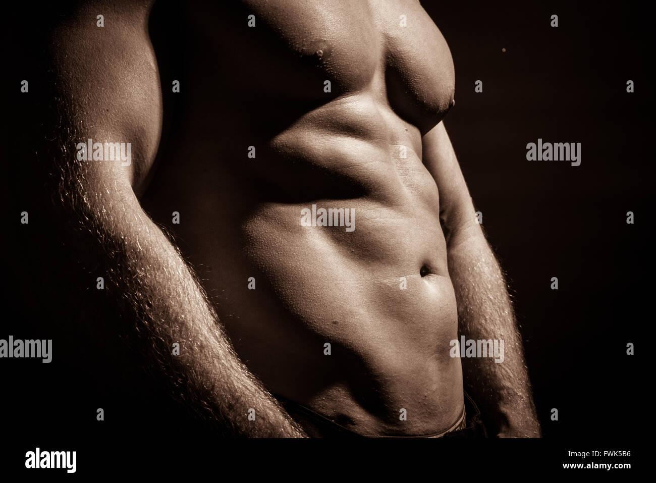 Mittelteil von nacktem Oberkörper muskulöser Mann stehend auf schwarzem Hintergrund Stockbild
