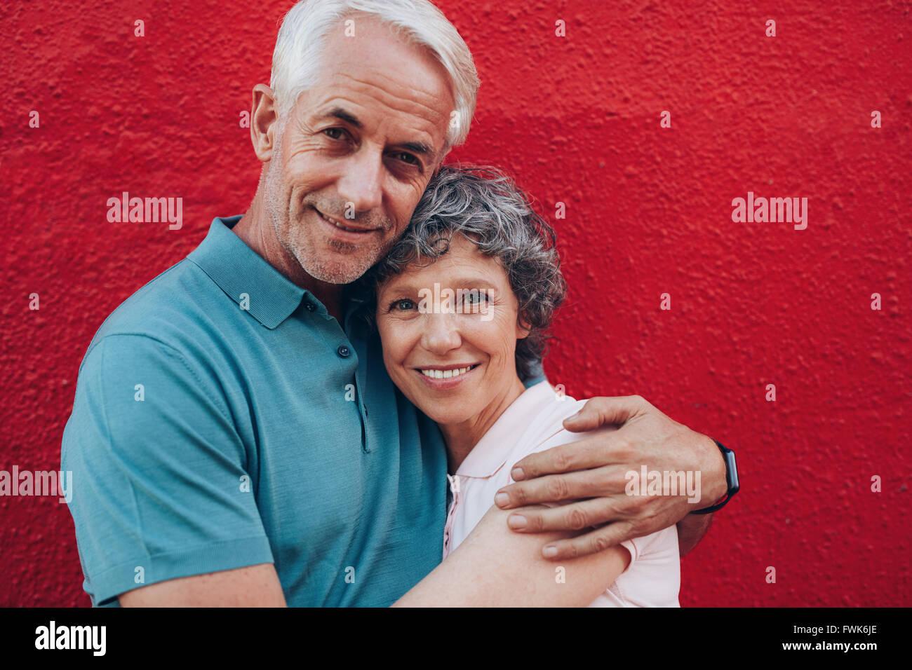 Porträt des Liebens Mitte im Alter paar umarmt vor rotem Hintergrund. Reifer Mann und Frau gemeinsam gegen Stockbild