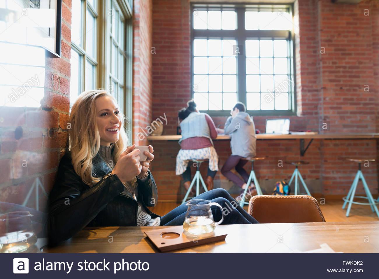 Lächelnde junge Frau trinken Tee im Café Stockbild