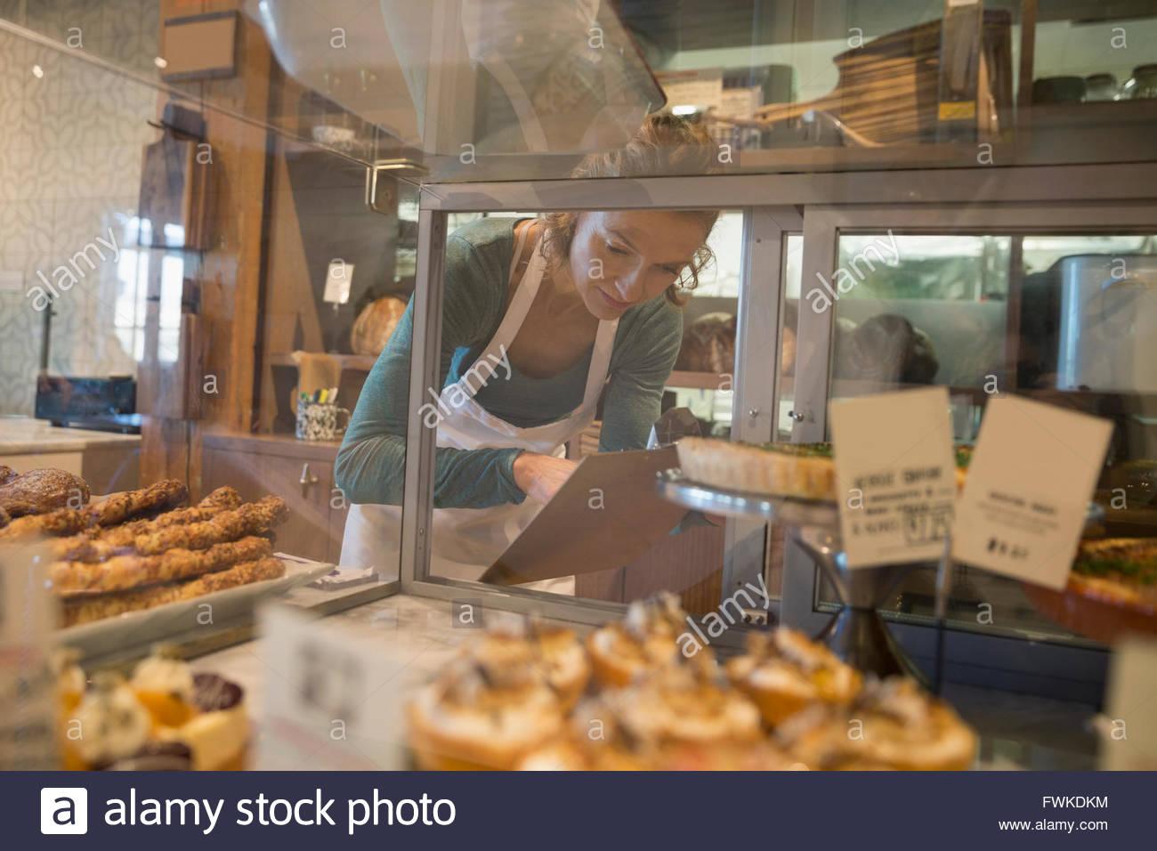 Bäckerei-Besitzer mit Zwischenablage Lagerbestand prüfen Stockbild