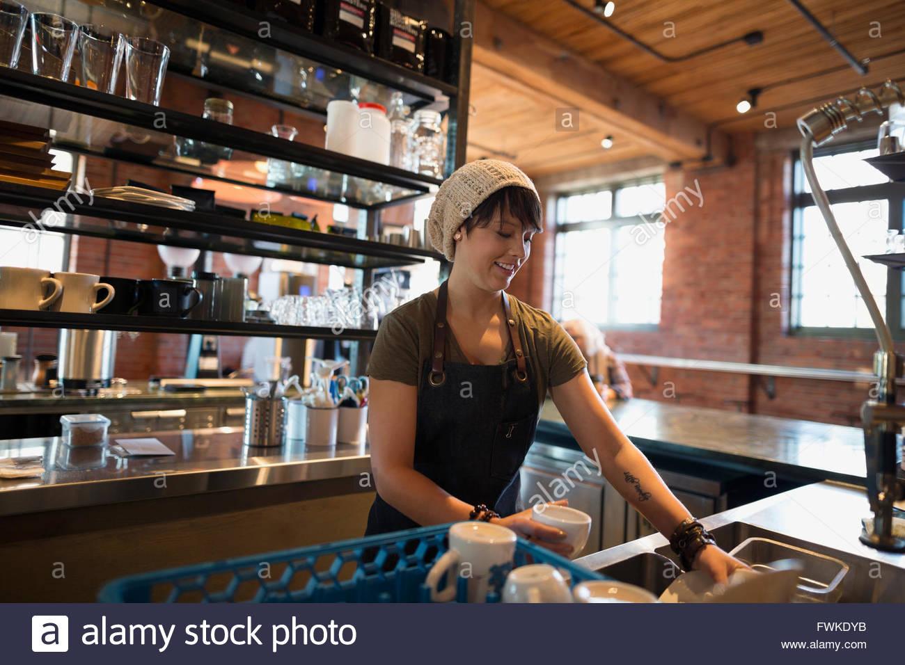 Arbeiter Geschirrspülen in Coffee-shop Stockbild