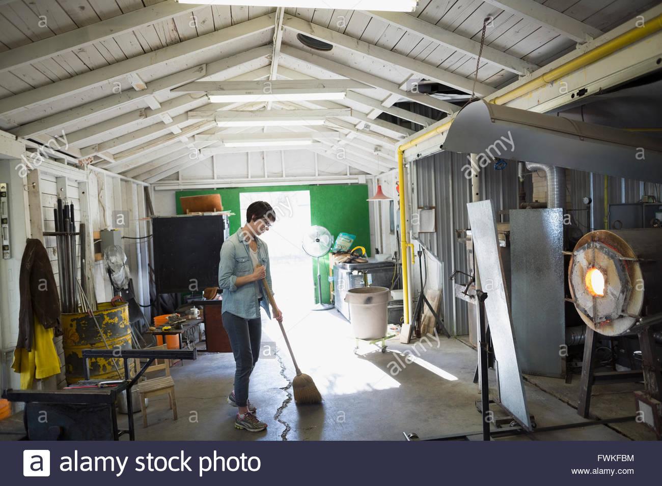 Weibliche Glasbläser fegen in Werkstatt Stockbild