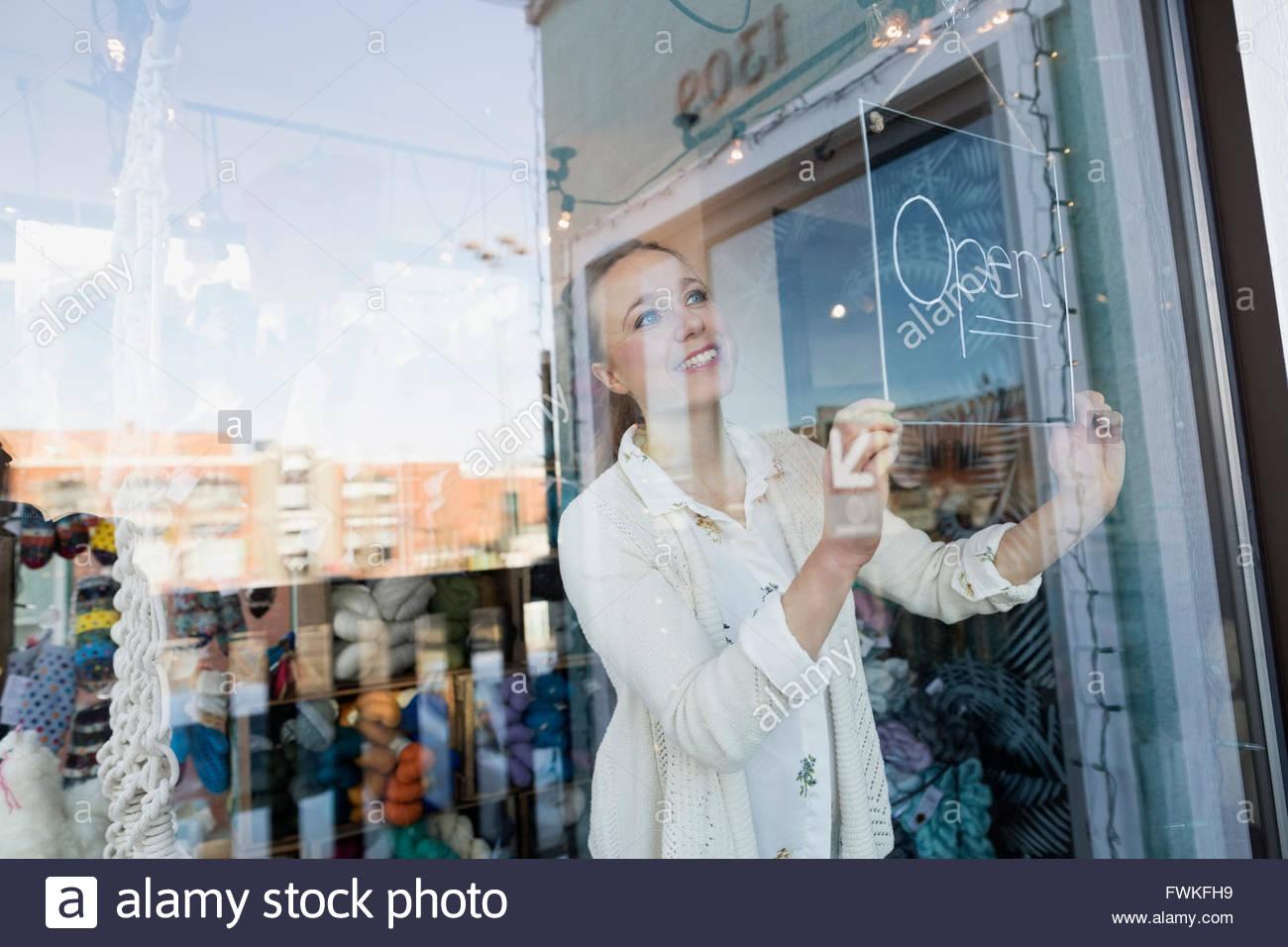 """Lächelnde Ladenbesitzer Schild """"geöffnet"""" am Fenster drehen Stockbild"""