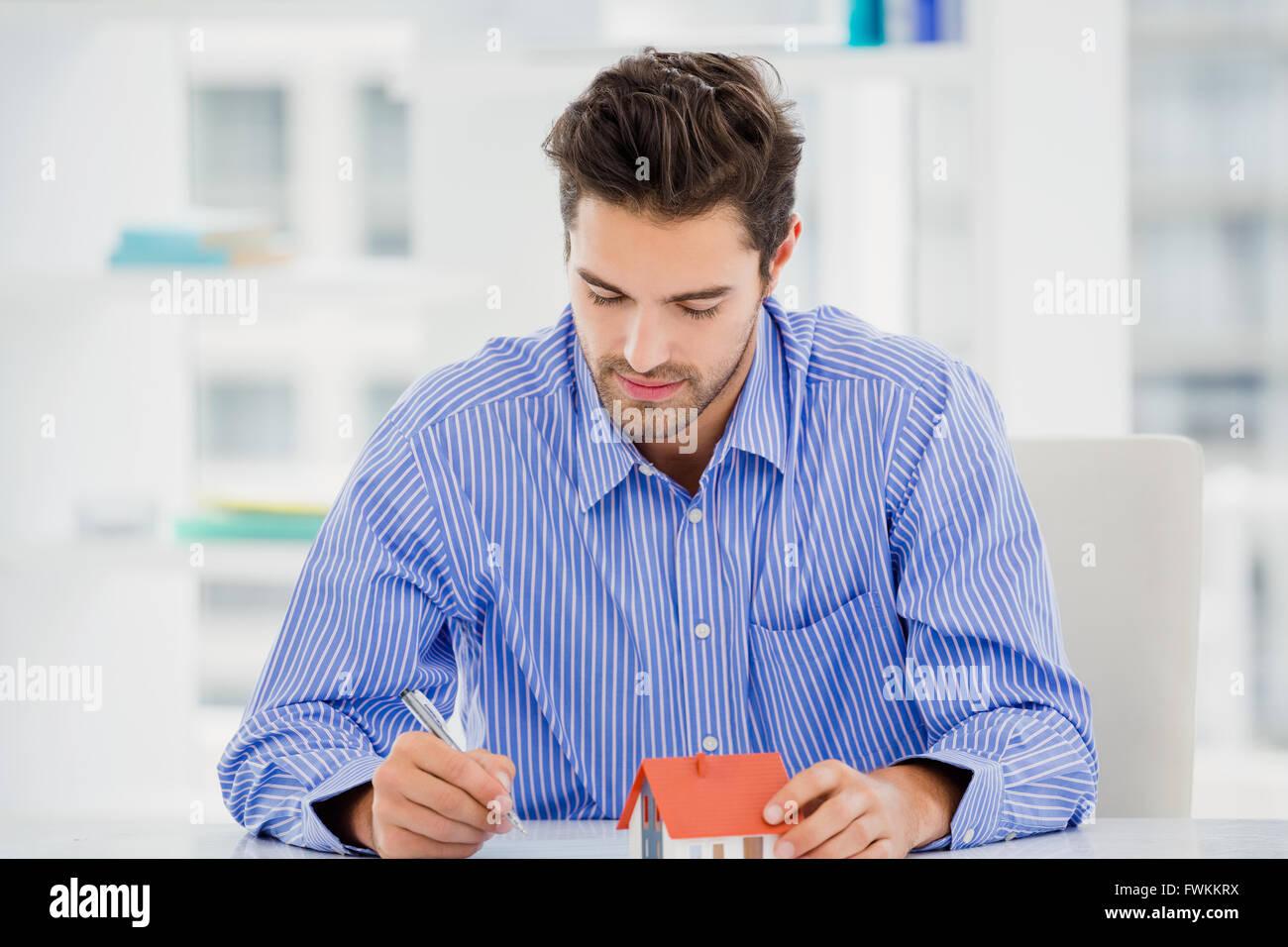Geschäftsmann mit einem Modell Haus und Schreiben auf Papier Stockbild