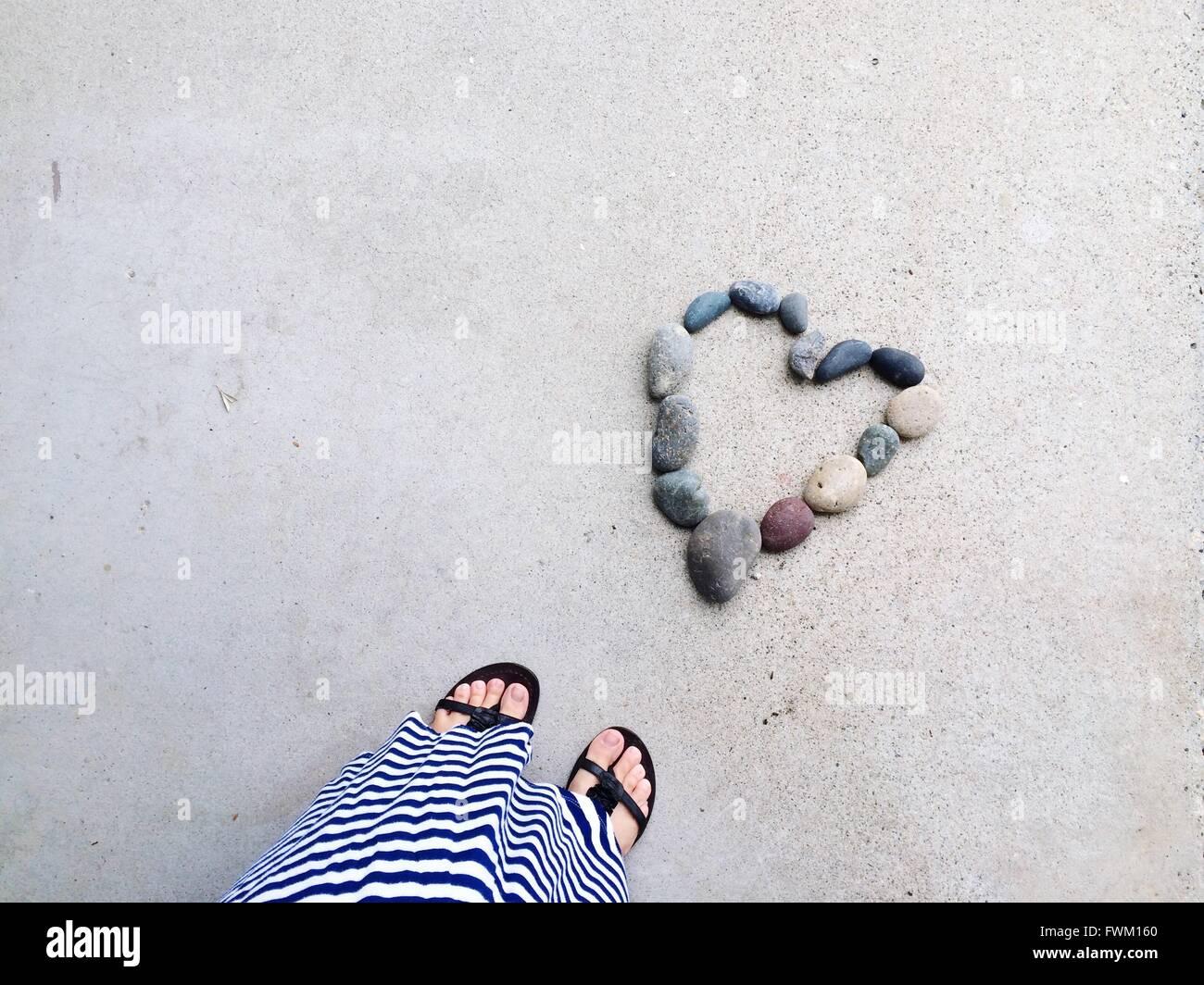 Geringen Teil der Frau mit Herz Form Kieselsteine am Strand Stockbild